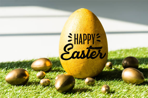 big ostrich egg with happy Easter lettering near golden chicken and quail eggs on green grass stock photo