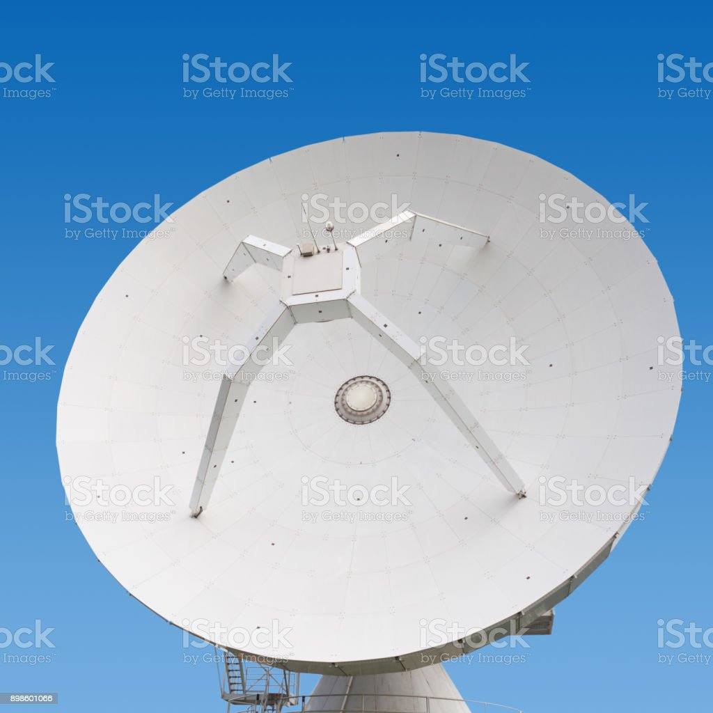 Big parabolic antenna at a day time with blue sky on background stock photo