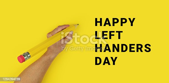 Big pencil in male left hand on yellow background with text Happy Left Handers Day. Conceptual banner for celebration of international left-handed day