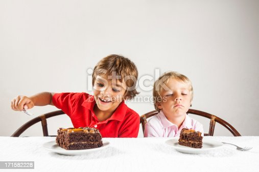 A conceptual photograph depicting inequality between two brothers, one with a very large slice of chocolate cake and the other with a small slice.Please browse: