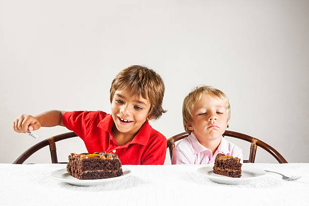 big piece of cake and a little one, inequality concept. - big cake stock photos and pictures