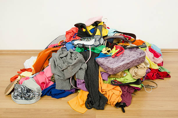 Big pile of clothes and accessories thrown on the ground. stock photo