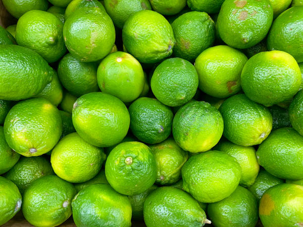 big pile of fresh lemons limes stacked at fruit stand farmers market grocery store stock photo