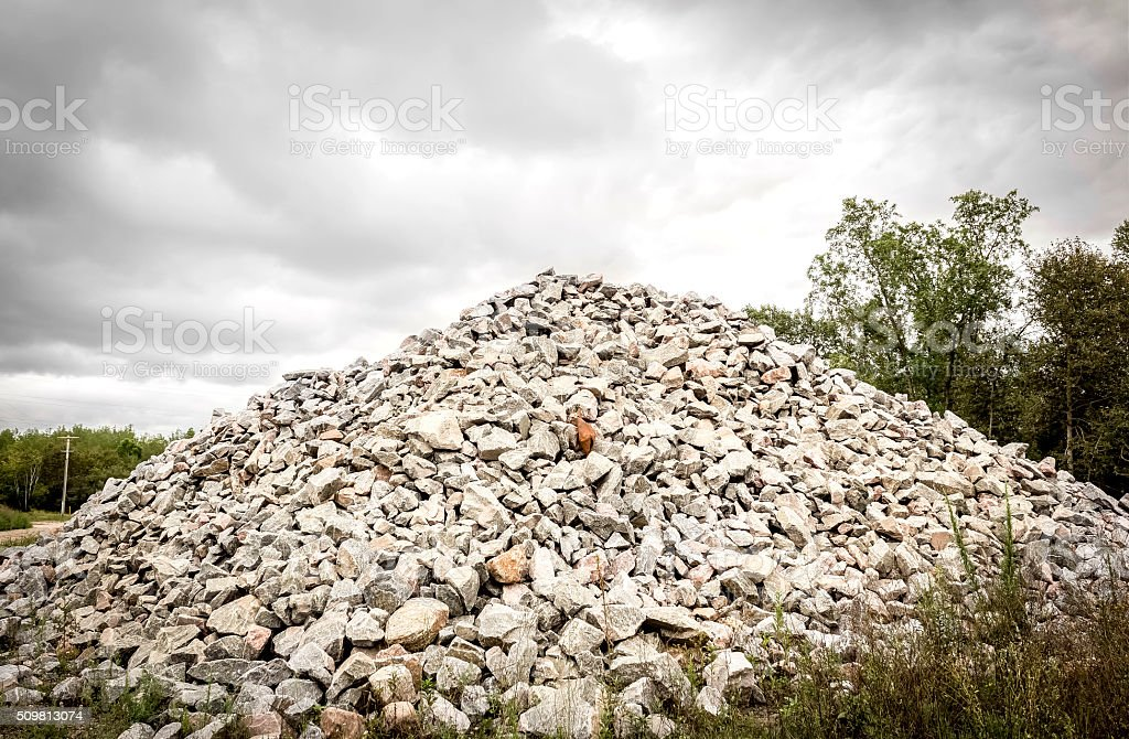 horizontal image of a large pile of rocks heaped up to a peak under a...