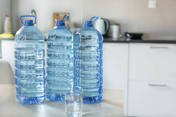Big plastic bottle with water on the table over bright kitchen backgroung. Bottle of clear transarent water in a blue color cap and handle closeup. gallon stock pictures, royalty-free photos & images