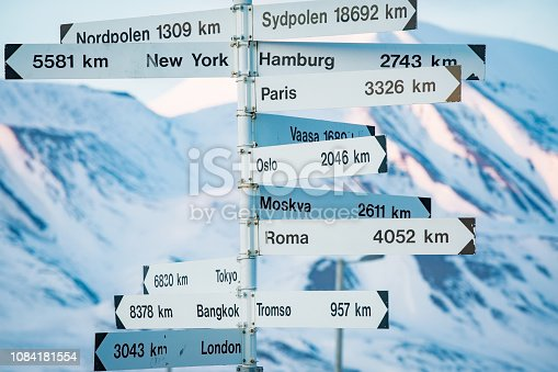 istock Big pole with directions signs and distances to cities 1084181554