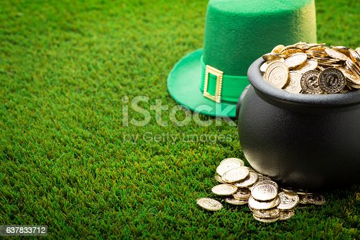 This is a close up photo of a large black pot of gold on the grass with a green hat symbolizing St. Patrick's Day.