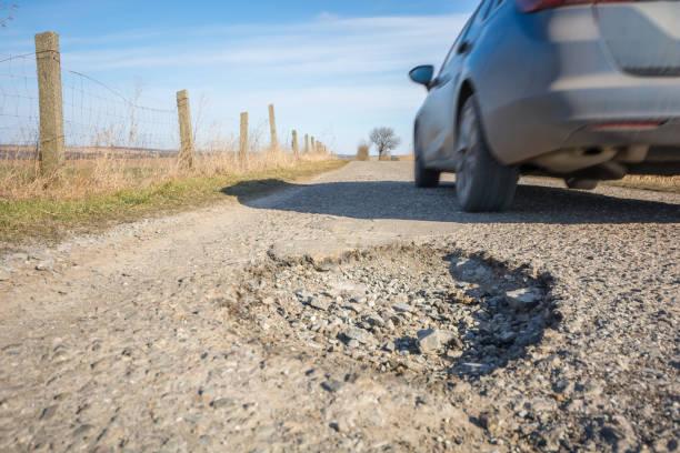 Großen Schlagloch auf einer Landstraße mit vorbeifahrenden Auto – Foto