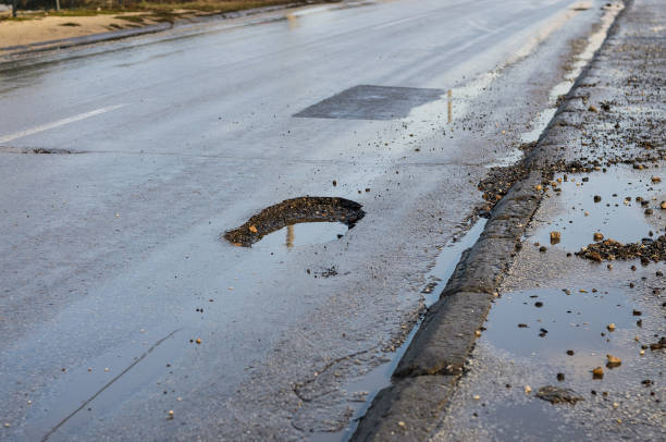 Big pothole on road after winter stock photo