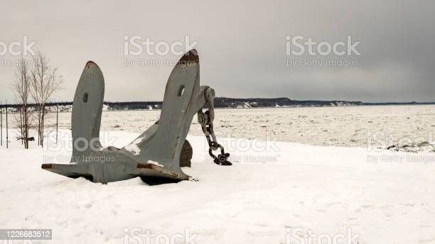 Photo of Big, real anchor on the snow at Port of Anchorage Small Boat Launch. Knik arm in the back full of melted, moving ice.