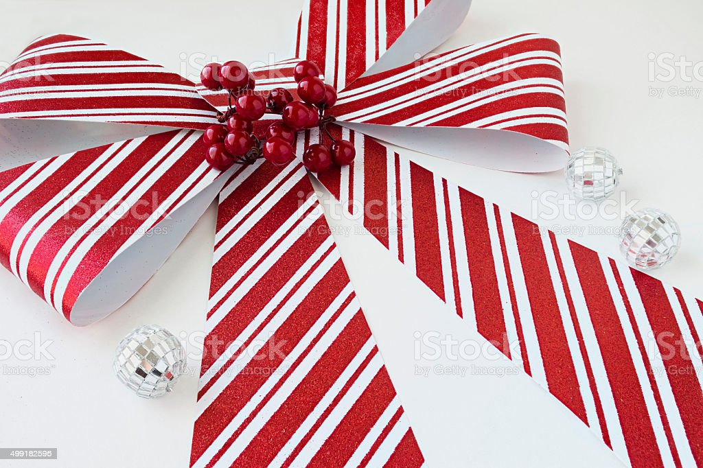 big red and white striped christmas bow on white background stock photo
