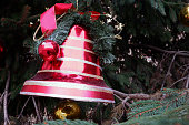 Big, red christmas bell ornament hanging on the Christmas tree. Close-up with copy space.