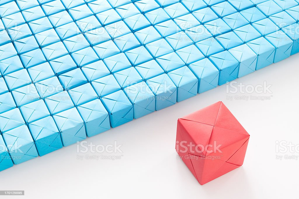Big red cube in front of blue ones stock photo