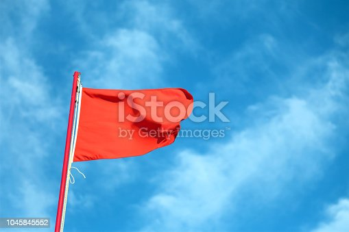 big red flag waving in the wind with the background of the blue sky and some clouds