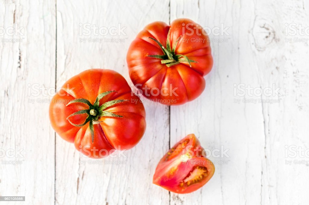Big Red Fresh tomatoes  whole and halved on old wooden table in rustic style, top view stock photo