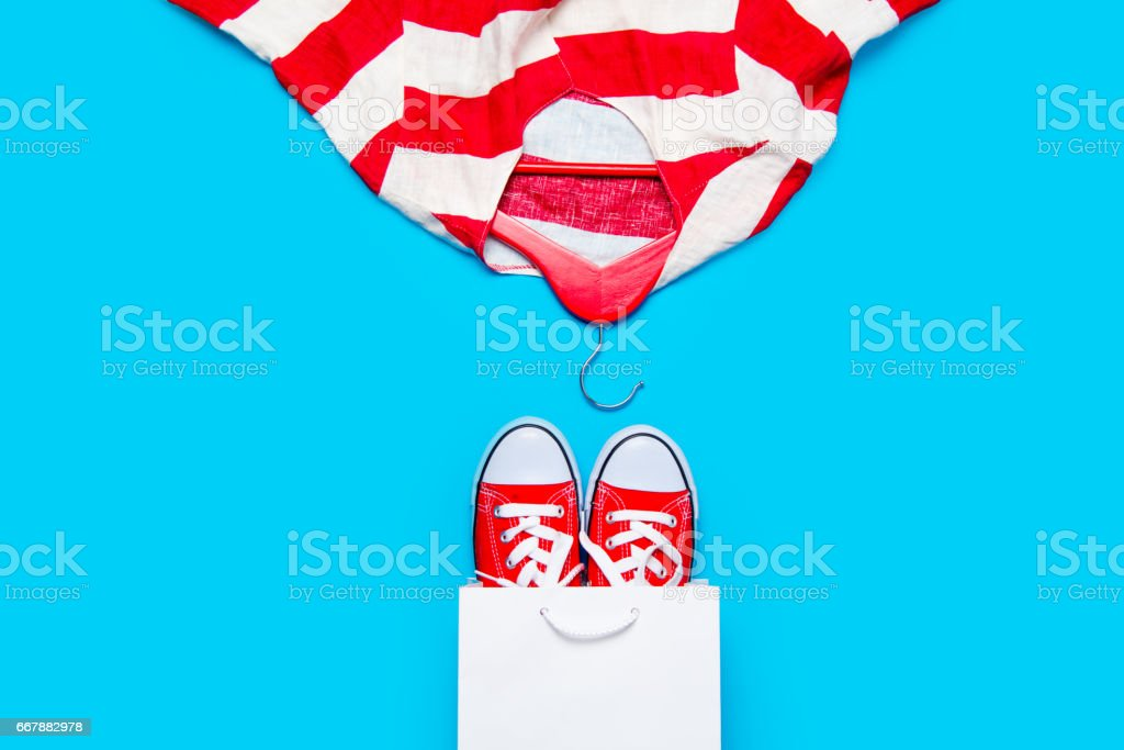 big red gumshoes in cool shopping bag and stried jacket on hanger on the wonderful blue background royalty-free stock photo
