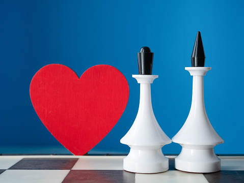 istock big red heart and two chessman king and queen aside on blue background. great wedding invitation idea 1129677222