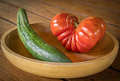 A big red heart-shaped tomato and cucumber