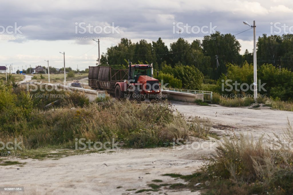 big red tractor driving on a rural road stock photo
