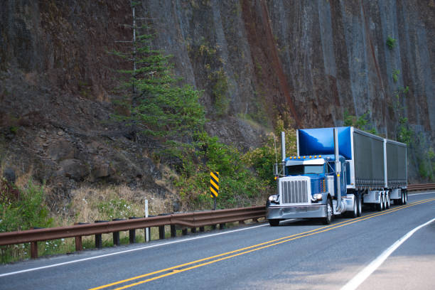 Big rig American bonnet semi truck with two covered black dry van semi trailers running on mountain road around huge cliff stock photo