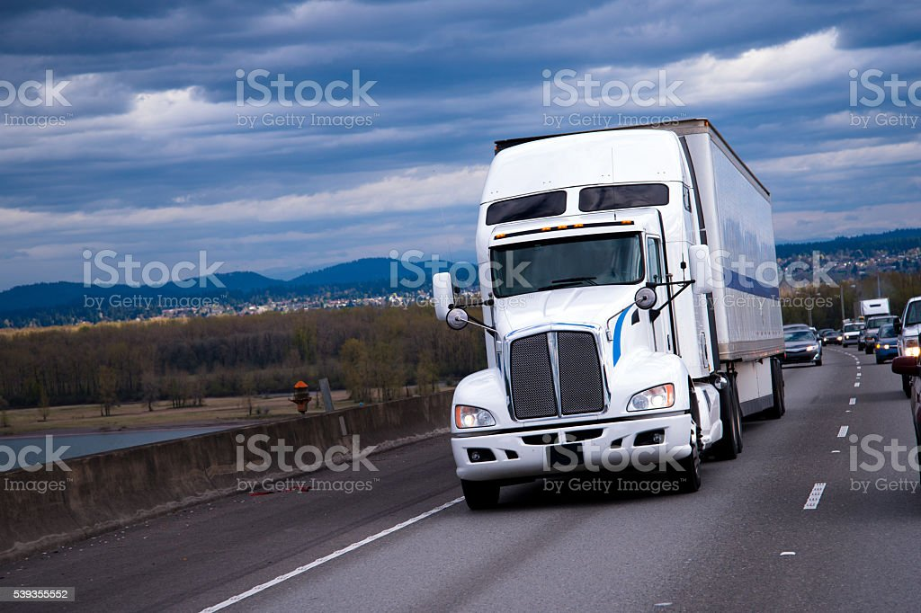 Big Rig American semi truck carring cargo on highway stock photo