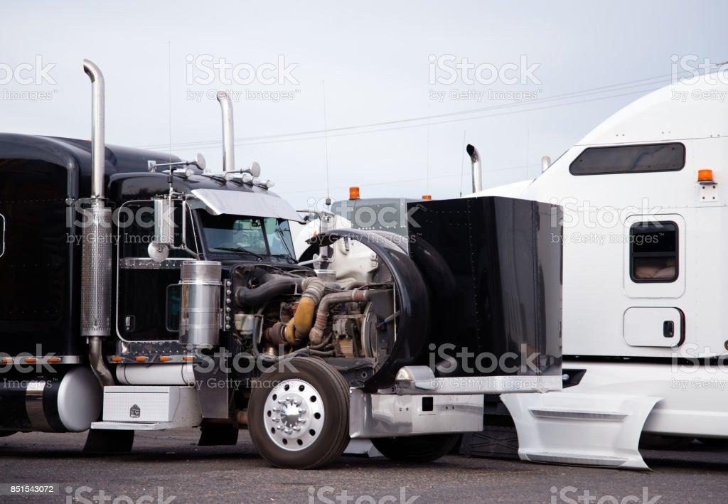 Aparejo grande negro semi camión tractor con capucha abierta preparar el motor para el próximo viaje de fraight en fila con otros camiones semi - foto de stock