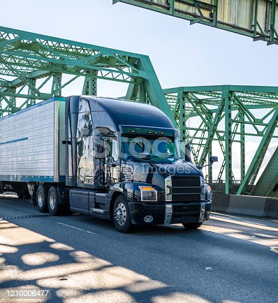 Big rig black stylish diesel long haul industrial semi truck transporting frozen commercial cargo in refrigerator semi trailer running on the arched truss Columbia River Interstate Bridge