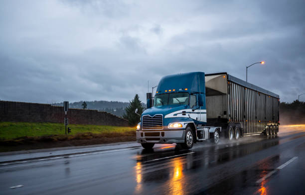 Big rig bonnet blue semi truck transporting cargo in covered bulk semi trailer running on the wet glossy road with raining weather evening stock photo