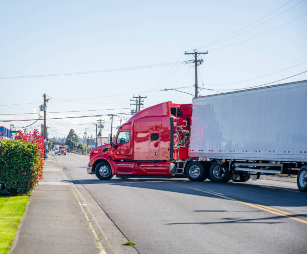 Big rig bonnet red semi truck with semi trailer turning from city street to truck stop entrance stock photo