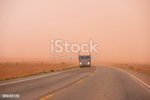 Big rig American bonnet car hauler semi truck with turn on headlight running on the road with very poor visibility in the red sand dust during huge sandstorm in Arizona