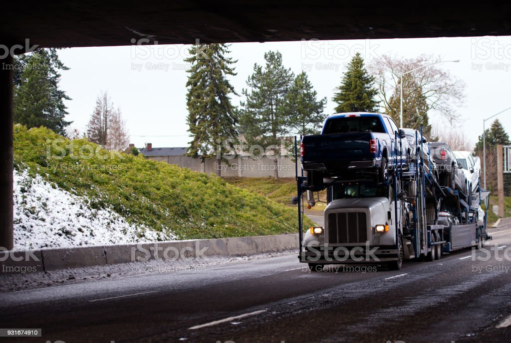 Big rig car hauler semi truck transporting cars on special semi trailer going by highway with bridge in winter weather stock photo