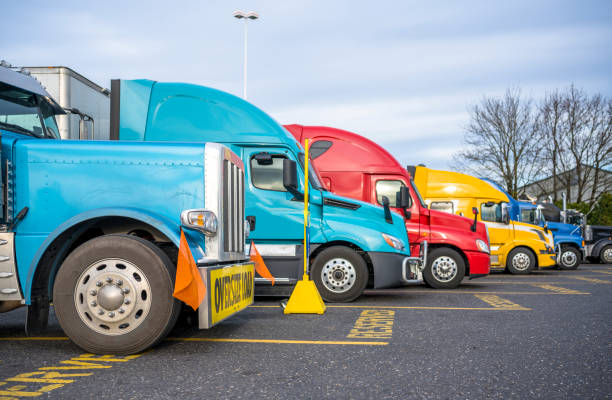 Big rig classic blue semi truck with oversize load sign standing in row with another semi trucks with semi trailers on reserved parking spots on truck stop stock photo