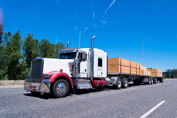 big rig klassischen semi truck flat bed anhänger tragen holz - aufgemotzte trucks stock-fotos und bilder