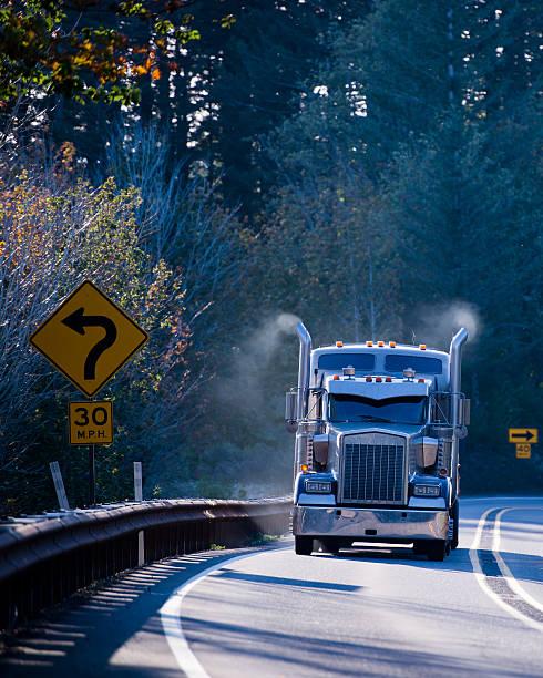big rig dark semi truck in sunshine with smoking pipes - aufgemotzte trucks stock-fotos und bilder