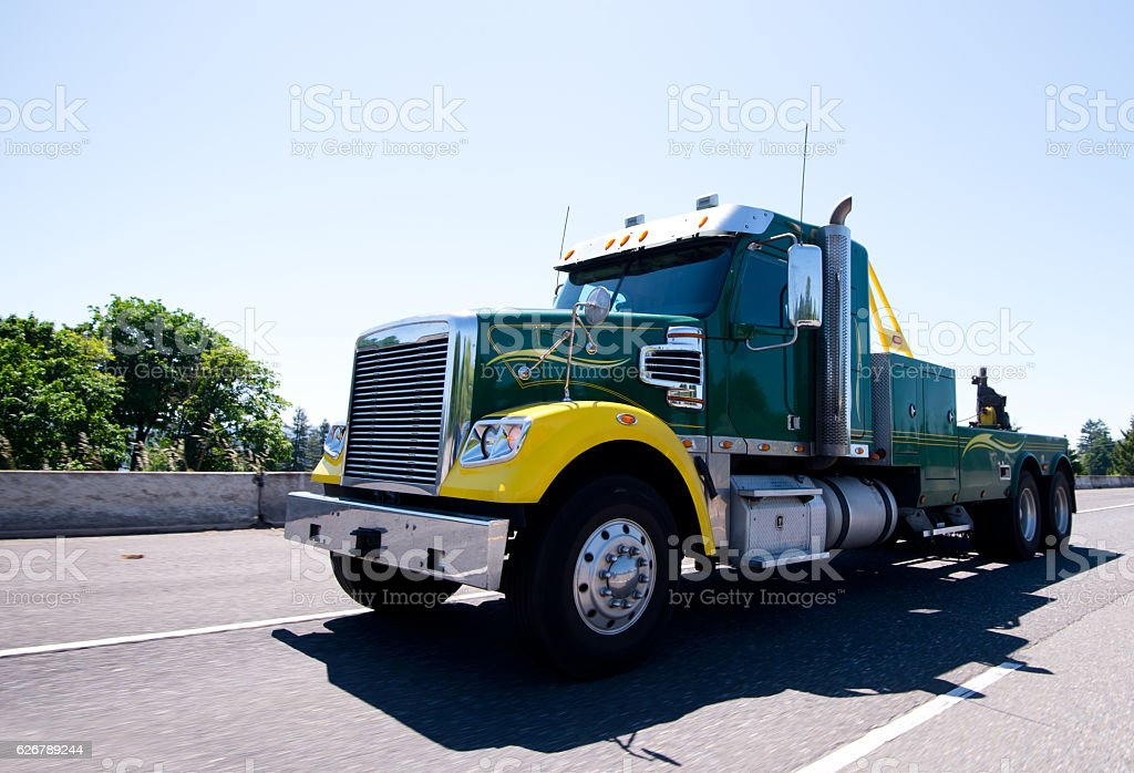 Big rig equipped towing semi truck on road stock photo