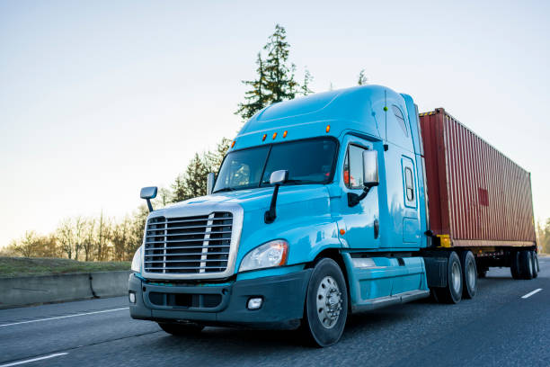 Big rig long haul semi truck transporting container on the highway stock photo
