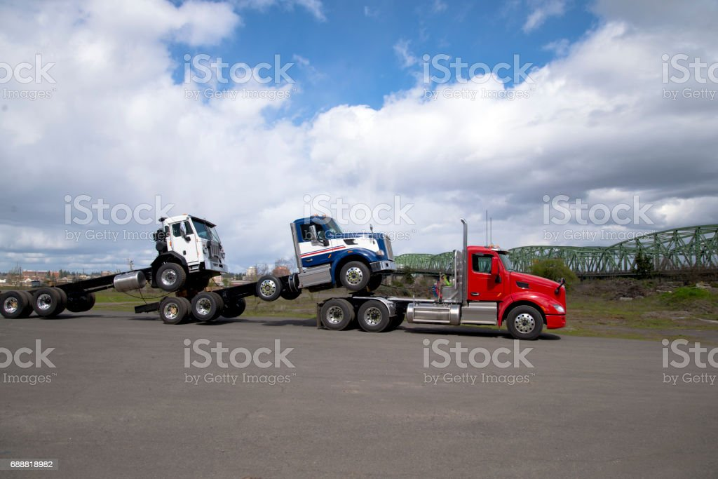 Big rig powerful semi truck transports two other trucks loaded one on the other stock photo
