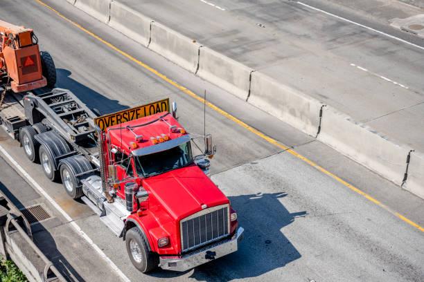 big rig red semi truck met oversize load teken op het dak het vervoeren van oversized apparatuur op de oplegger - te groot stockfoto's en -beelden