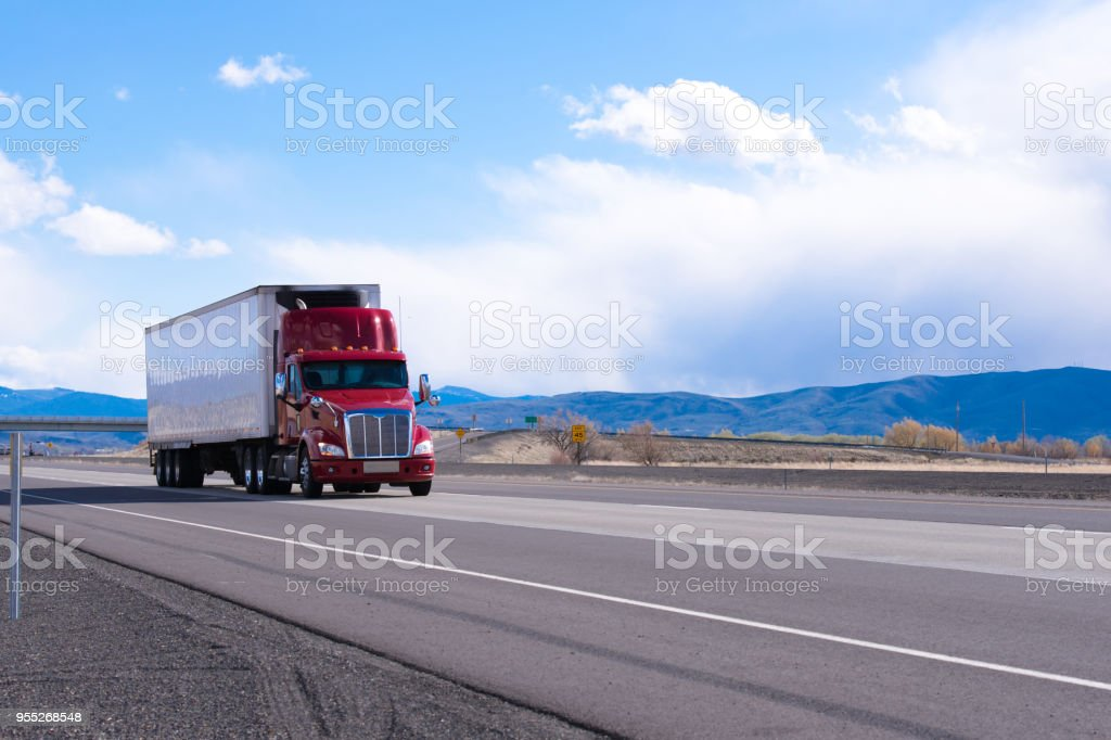 Big rig red semi truck with refrigerated semi trailer transporting commercial cargo on flat road in Utah stock photo
