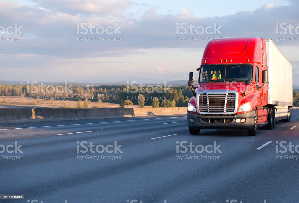 Big rig red semi truck with trailer on wide highway stock photo