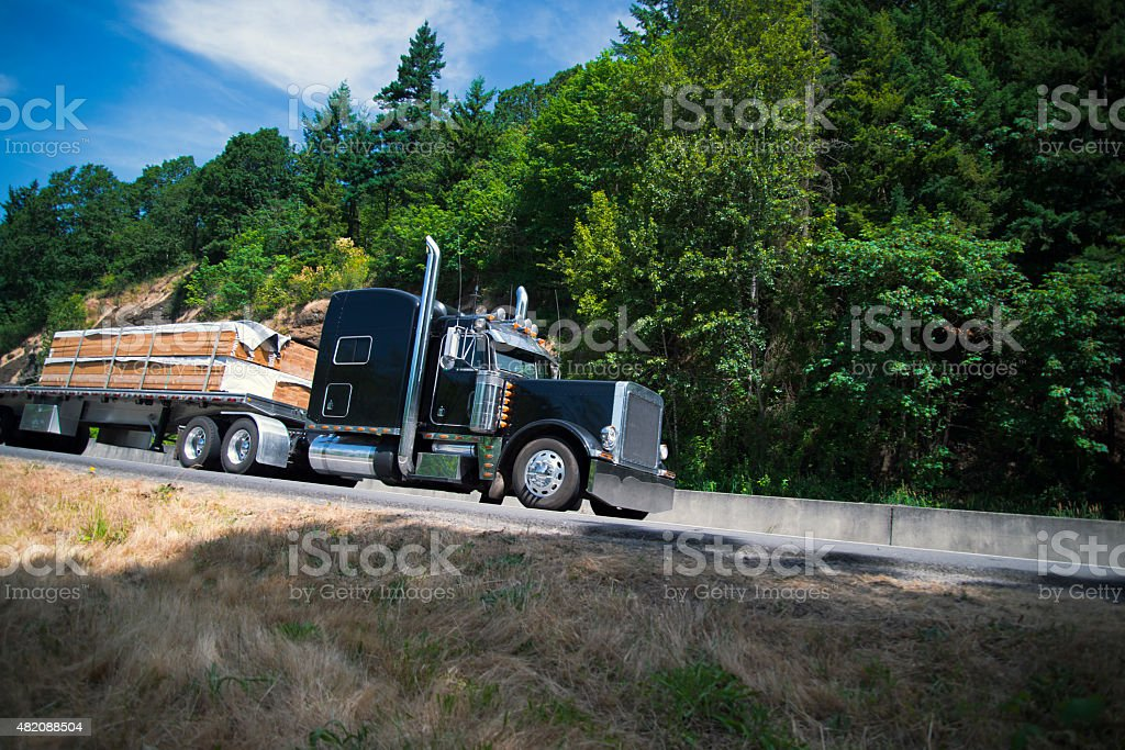 Big rig semi truck carry lumber flat bed trailer stock photo