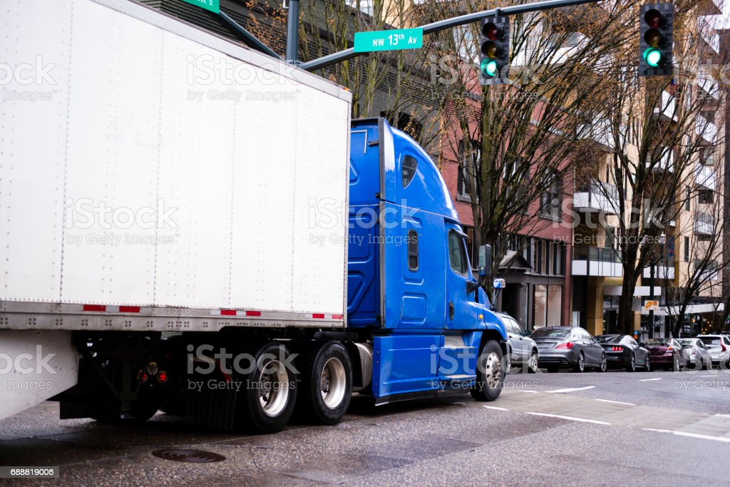 Big rig semi truck in blue with trailer moving by urban city street with modern building and cars stock photo
