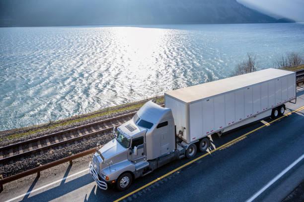 big rig semi truck transporting cargo in dry van semi trailer running on sunny road along wide river - autotransporter stock-fotos und bilder