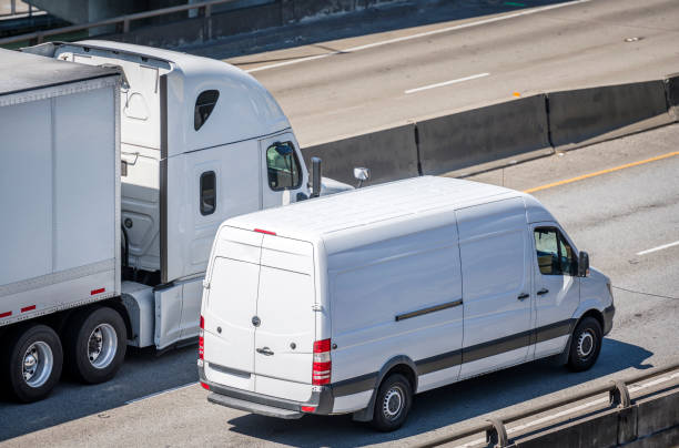 Big rig semi truck with dry van semi trailer and compact cargo mini van driving side by side on the multiline highway road stock photo