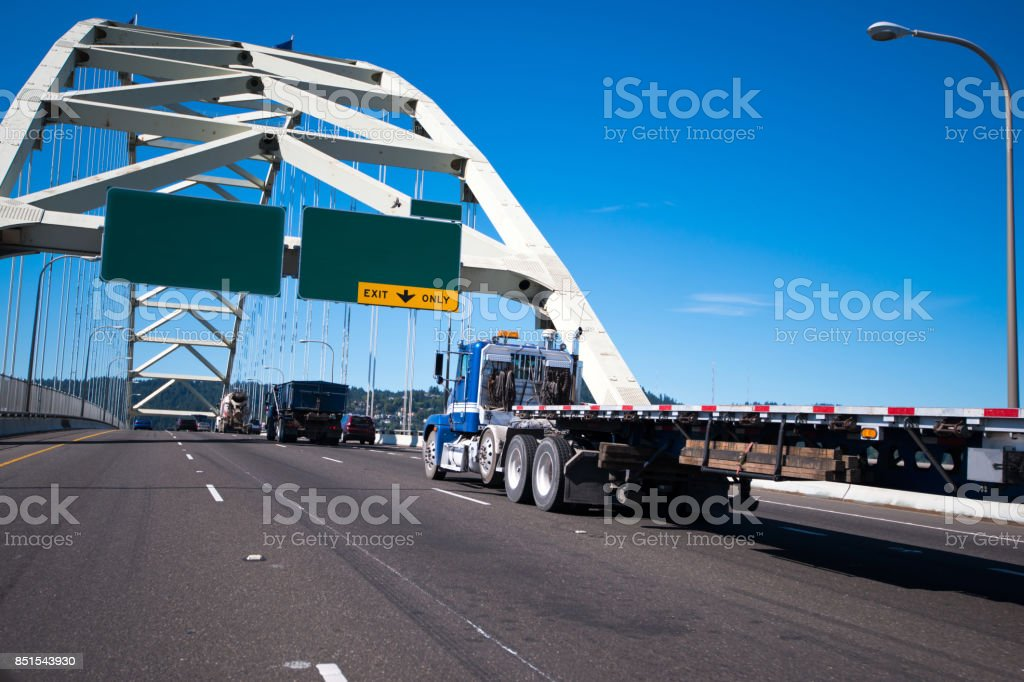 Big rig semi truck with flat bed trailer driving over arched Fremont bridge stock photo