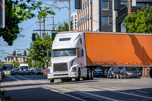 White classic industrial diesel big rig semi truck tractor transporting commercial cargo in orange dry van semi trailer turning on the crossroad street intersection with busy city traffic