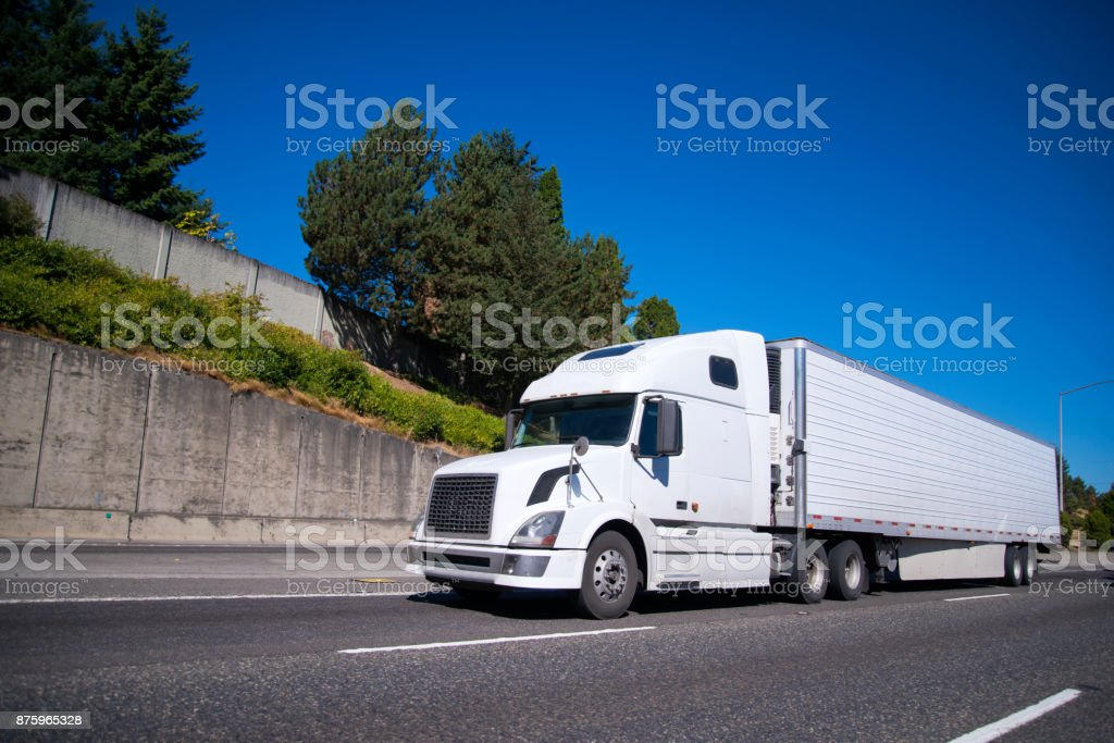 Big rig semi truck with reefer semi trailer going on highway with commercial cargo for delivery stock photo