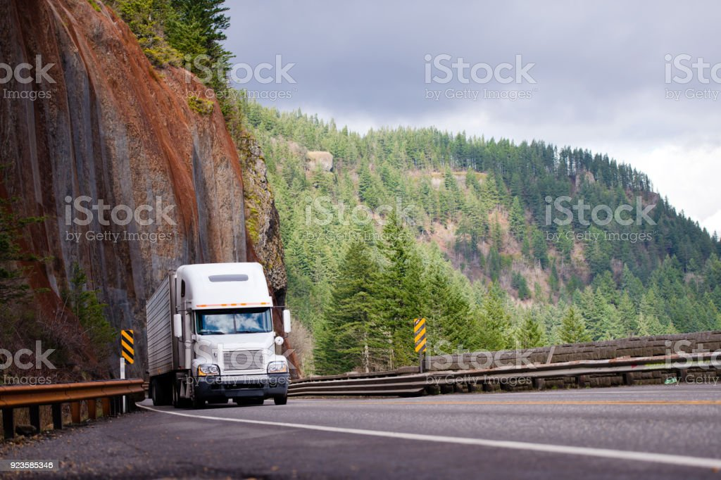 Big rig semi truck with reefer trailer transporting cargo on winding road with with a rock on one side and a precipice on the other stock photo