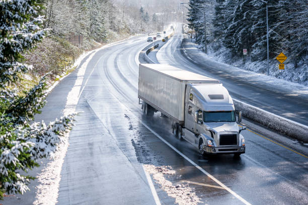 Big rig semi truck with semi trailer driving on winter snowy highway with wet melting snow surface stock photo