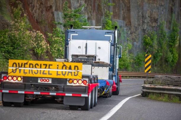 big rig semi truck met teken oversized belasting achter platte bed semi-trailer rijden op de bergweg met rock muur aan de zijkant - te groot stockfoto's en -beelden